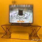 طاوله تلفاز باللون الذهبي والزجاج بلون الموكا.